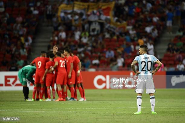 Manuel Lanzini of Argentina looks on as Singapore players huddle during the International Test match between Argentina and Singapore at National...