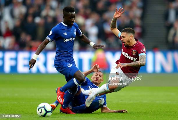 Manuel Lanzini of West Ham United is challenged by Idrissa Gueye and Richarlison of Everton during the Premier League match between West Ham United...
