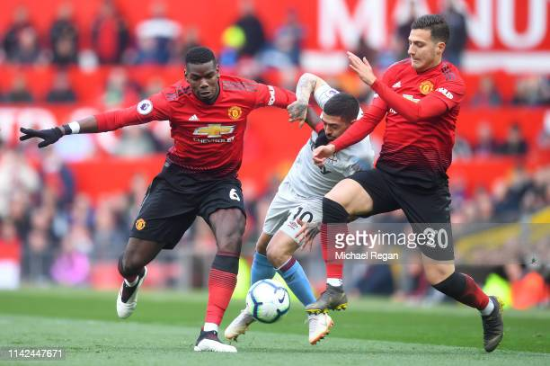 Manuel Lanzini of West Ham United is challenged by Paul Pogba of Manchester United and Diogo Dalot of Manchester United during the Premier League...