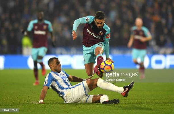 Manuel Lanzini of West Ham United is tackled by Mathias Jorgensen of Huddersfield Town during the Premier League match between Huddersfield Town and...