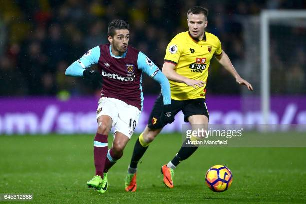Manuel Lanzini of West Ham United us chased by Tom Cleverly of Watford during the Premier League match between Watford and West Ham United at...