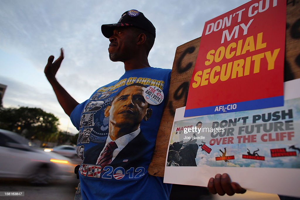 Manuel Lloyd along with other protesters rally together outside the office of U.S. Sen. Marco Rubio (R-FL) on December 10, 2012 in Doral, Florida. The protesters are hoping that Senators like Rubio will not cut medicare/social security benefits and will agree to raise taxes on the top 2% of earners in the country.