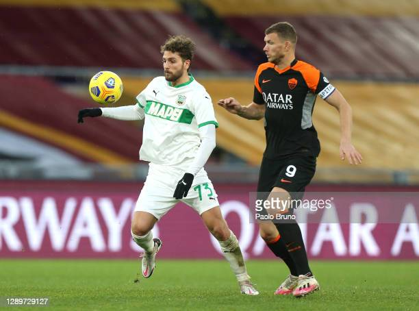 Manuel Locatelli of US Sassuolo battles for possession with Edin Dzeko of Roma during the Serie A match between AS Roma and US Sassuolo at Stadio...
