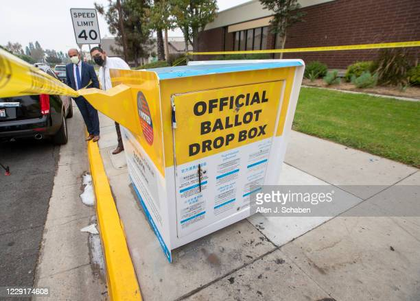 Manuel Lozano, left, Baldwin Park mayor, and Sam Gutierrez, director of public works, view the fire damage to the official ballot drop box where...