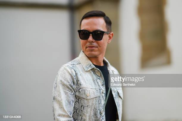 Manuel Luhas wears black sunglasses, a black t-shirt, a gray with black snake print pattern jacket, during Feeric Fashion Week 2021, on July 22, 2021...