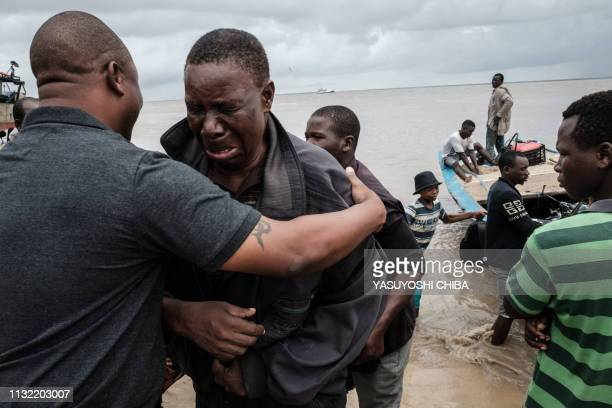 Manuel Machacawa Maezane cries as he meets his son Aristides after being evacuated from Buzi, on the beach in Beira, Mozambique, on March 23, 2019. -...