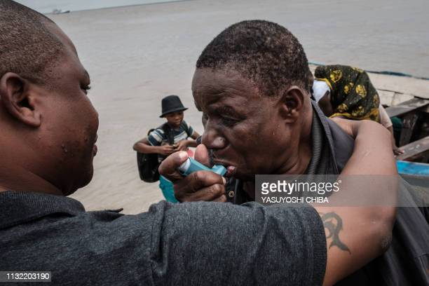 Manuel Machacawa Maezane takes an asthma puffer as he meets his son Aristides after being evacuated from Buzi on the beach in Beira Mozambique on...