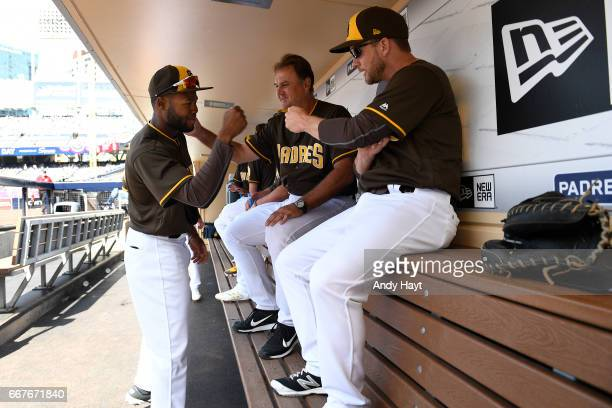 Manuel Margot greets Glenn Hoffman and Andy Green of the San Diego Padres in the dugout prior to the game on Opening Day against the San Francisco...
