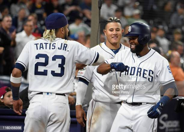 Manuel Margot of the San Diego Padres is congratulated by Manny Machado and Fernando Tatis Jr #23 after hitting a solo home run during the eighth...