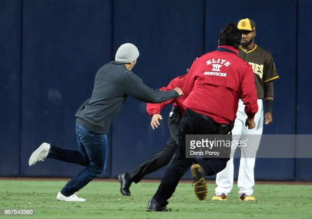 Manuel Margot of the San Diego Padres looks on as a fan tries to evade security guards during the eighth inning of a baseball game against the St...