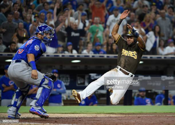 Manuel Margot of the San Diego Padres scores ahead of the throw to Willson Contreras of the Chicago Cubs during the eighth inning of a baseball game...