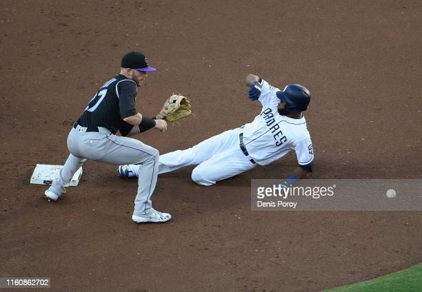 Manuel Margot of the San Diego Padres slides into second base ahead of the throw to Trevor Story of the Colorado Rockies during the second inning of...