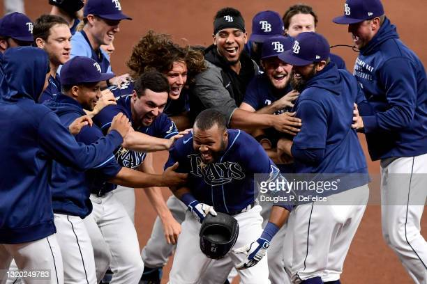 Manuel Margot of the Tampa Bay Rays is mobbed by his teammates after hitting an RBI single during the tenth inning to defeat the Kansas City Royals...