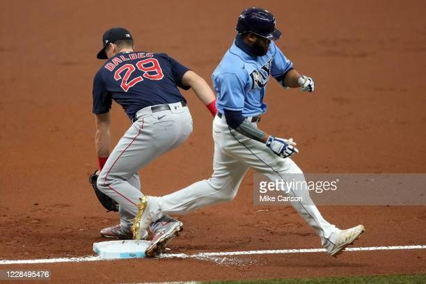 Manuel Margot of the Tampa Bay Rays reaches first base on a bunt as Bobby Dalbec of the Boston Red Sox misses the base with his foot in the first...