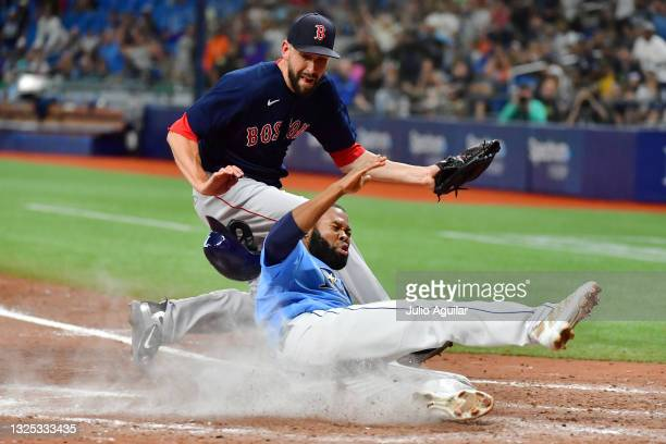 Manuel Margot of the Tampa Bay Rays slides home in the ninth inning after Matt Barnes of the Boston Red Sox threw a wild pitch at Tropicana Field on...