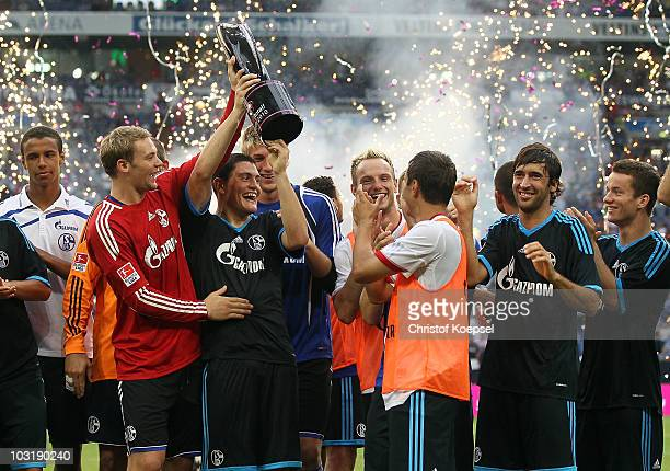 Manuel Neuer and Kyriakos Papadopoulos of Schalke hold the winning trophy after winning 31 the LIGA total Cup 2010 final match between FC Bayern...