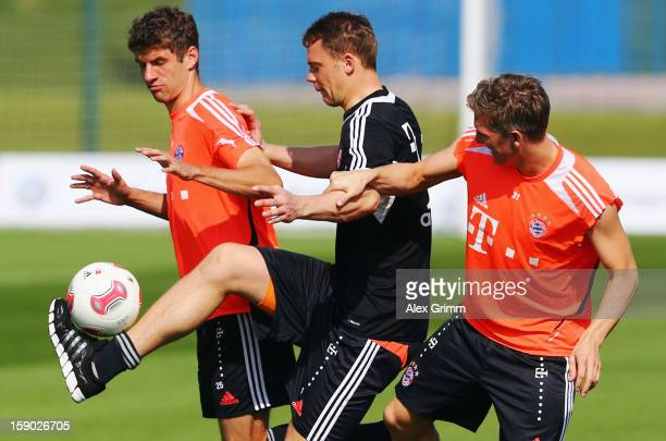 Manuel Neuer is challenged by Thomas Mueller and Bastian Schweinsteiger during a Bayern Muenchen training session at the ASPIRE Academy for Sports...