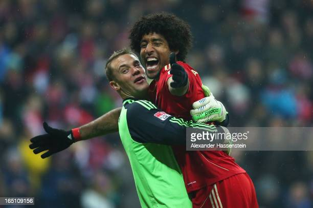 Manuel Neuer of Bayern Muenchen and team mate Dante celebrate their team's seventh goal during the Bundesliga match between FC Bayern Muenchen and...