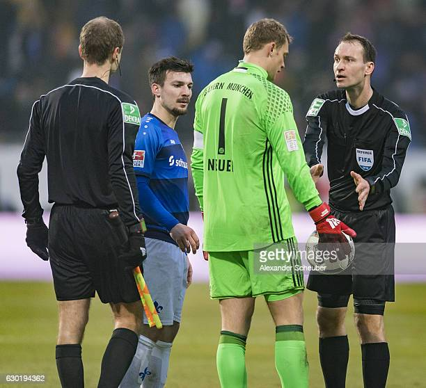 Manuel Neuer of Bayern Muenchen discusses with referee Bastian Dankert and drops the ball during to the Bundesliga match between SV Darmstadt 98 and...