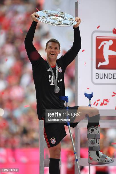 Manuel Neuer of Bayern Muenchen poses with the Championship trophy in celebration of the 67th German Championship title following the Bundesliga...
