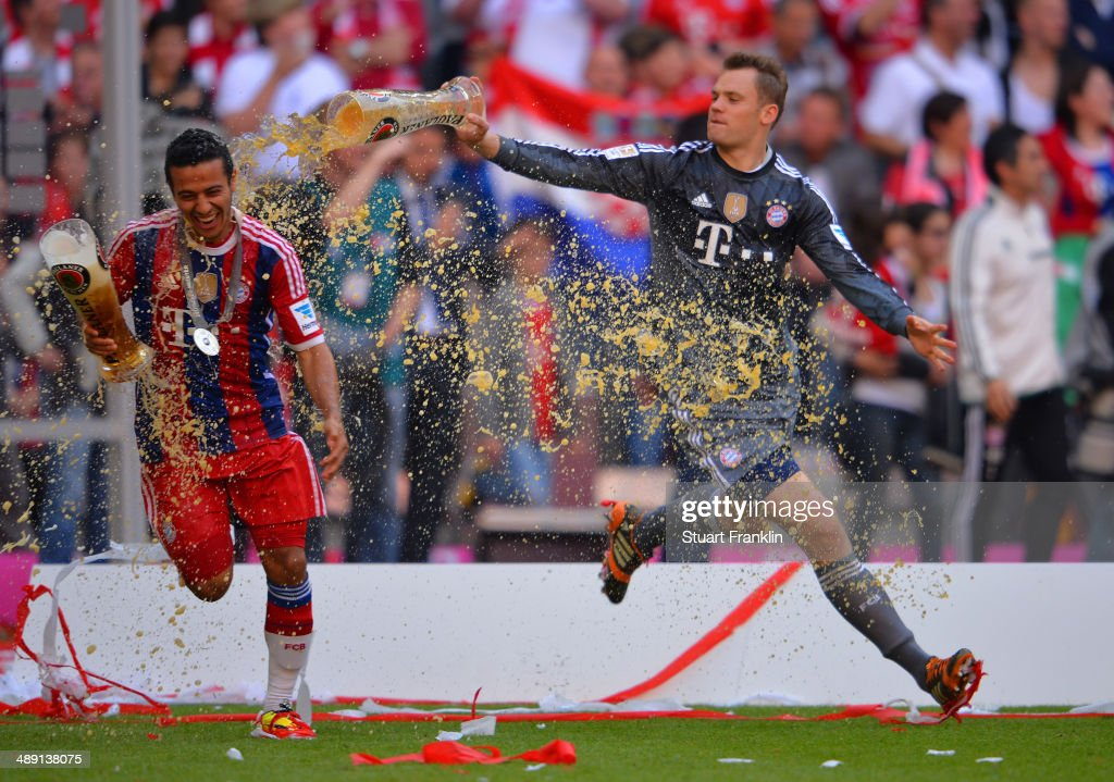 Manuel Neuer of Bayern Muenchen pours beer over Thiago Alcantara of Bayern Muenchen as they celebrate after the Bundesliga match between Bayern Muenchen and VfB Stuttgart at Allianz Arena on May 10, 2014 in Munich, Germany.