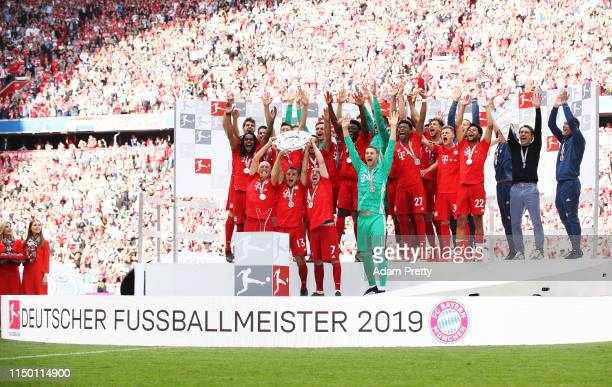 Manuel Neuer of Bayern Munich and team mates celebrate with the trophy following the Bundesliga match between FC Bayern Muenchen and Eintracht...