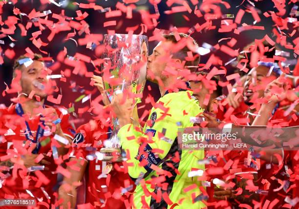Manuel Neuer of Bayern Munich kisses the UEFA Super Cup trophy as he celebrates victory over FC Sevilla at Puskas Arena on September 24, 2020 in...