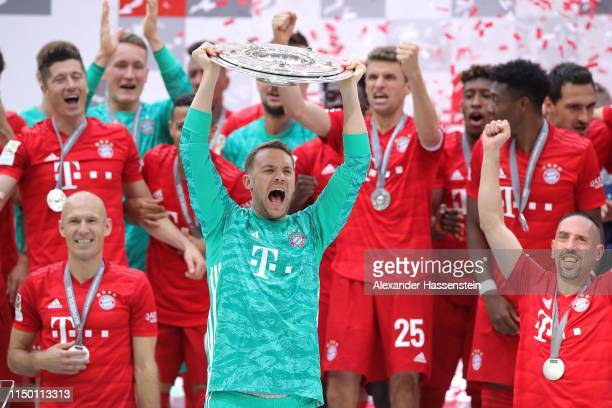 Manuel Neuer of Bayern Munich lifts the trophy following the Bundesliga match between FC Bayern Muenchen and Eintracht Frankfurt at Allianz Arena on...