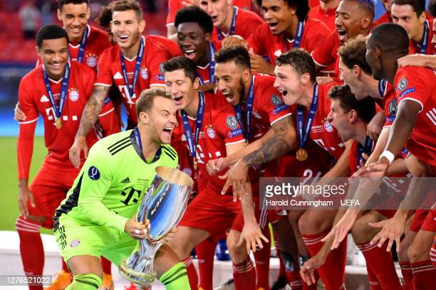 Manuel Neuer of Bayern Munich lifts the UEFA Super Cup trophy as he and team mates celebrate victory over FC Sevilla at Puskas Arena on September 24,...