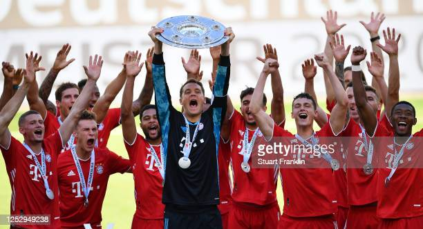 Manuel Neuer of FC Bayern Muenchen lifts the trophy to celebrate the championship following the Bundesliga match between VfL Wolfsburg and FC Bayern...
