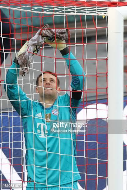 Manuel Neuer of FC Bayern Muenchen talks to Assistant Referee Lasse Koslowski about the goal net prior to the Bundesliga match between RB Leipzig and...