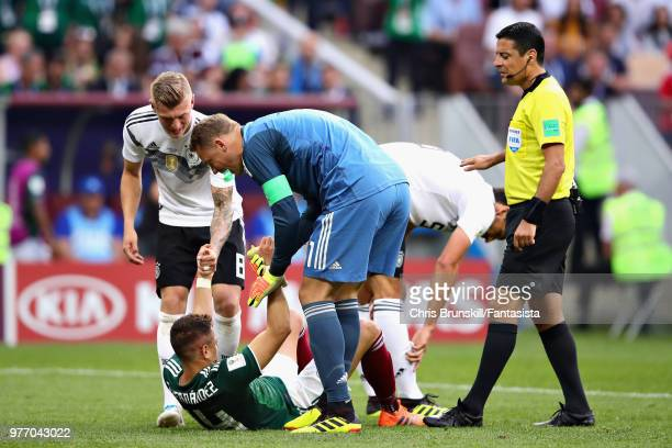 Manuel Neuer of Germany and teammate Toni Kroos help Javier Hernandez of Mexico to his feet as Referee Alireza Faghani looks on during the 2018 FIFA...