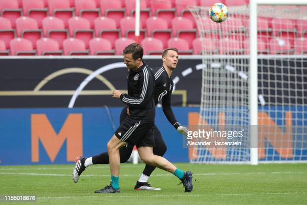 Manuel Neuer of Germany battles for the ball with team manager Oliver Bierhoff during a training session of the German national team at Opel Arena on...