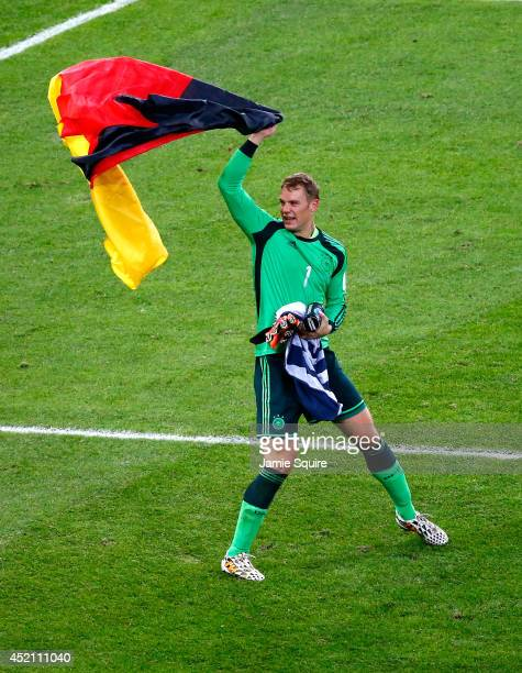Manuel Neuer of Germany celebrates with a German flag after defeating Argentina 10 in extra time during the 2014 FIFA World Cup Brazil Final match...