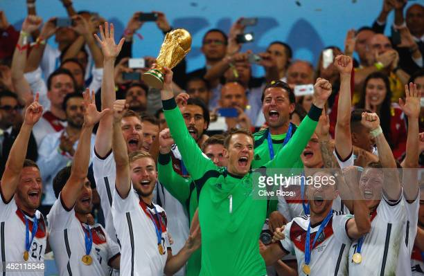 Manuel Neuer of Germany lifts the World Cup trophy with teammates after defeating Argentina 10 in extra time during the 2014 FIFA World Cup Brazil...