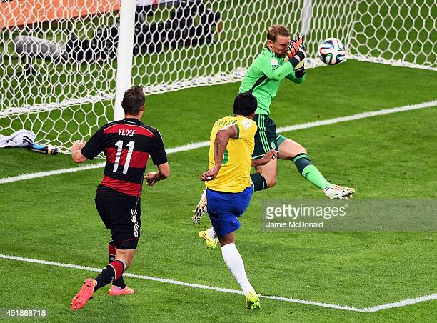 Manuel Neuer of Germany makes a save at a shot at goal by Paulinho of Brazil during the 2014 FIFA World Cup Brazil Semi Final match between Brazil...