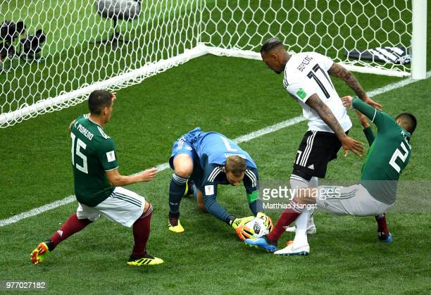 Manuel Neuer of Germany makes a save from Hugo Ayala and Hector Moreno of Mexico as Jerome Boateng of Germany protects the ball during the 2018 FIFA...