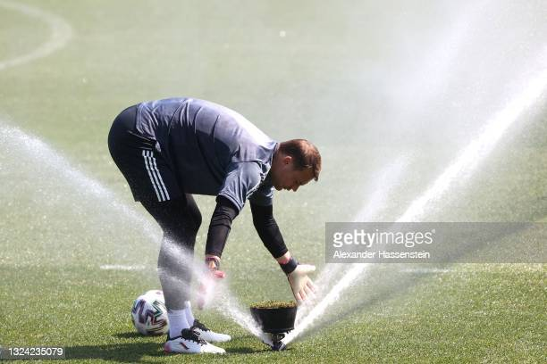 Manuel Neuer of Germany washes his gloves in a sprinkler during the Germany Training Session ahead of the Euro 2020 Group F match between Portugal...