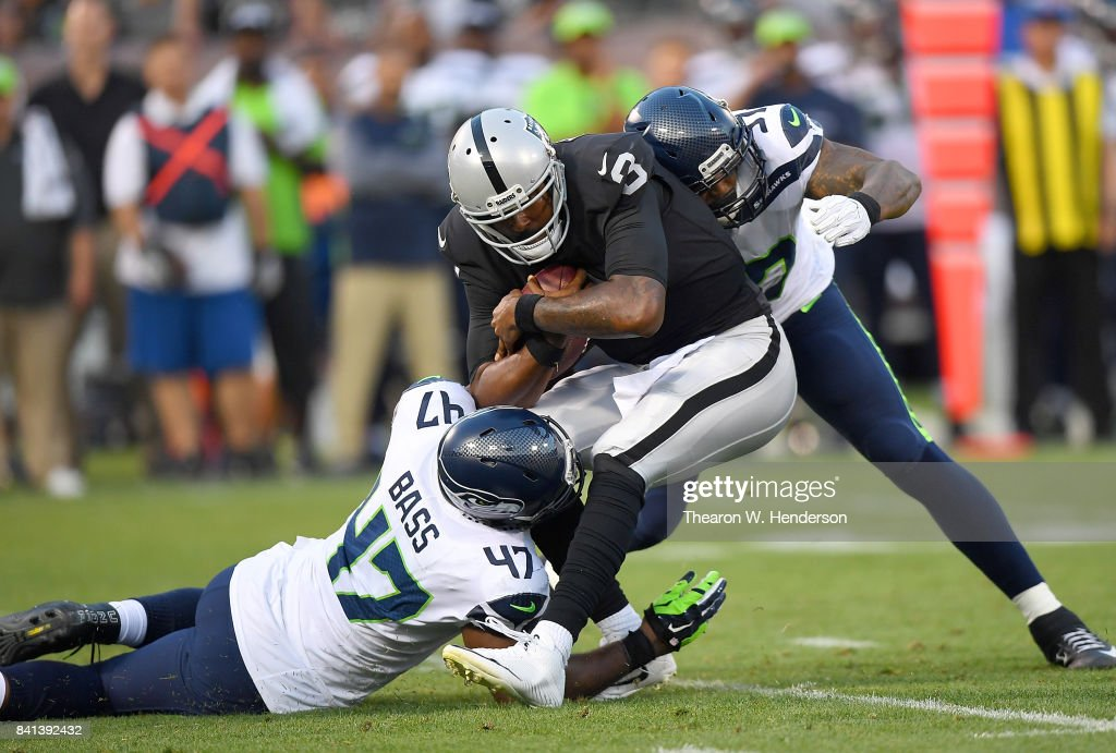EJ Manuel #3 of the Oakland Raiders gets tackled by David Bass #47 and Marcus Smith #97 of the Seattle Seahawks in the first quarter of their game at the Oakland-Alameda County Coliseum on August 31, 2017 in Oakland, California.