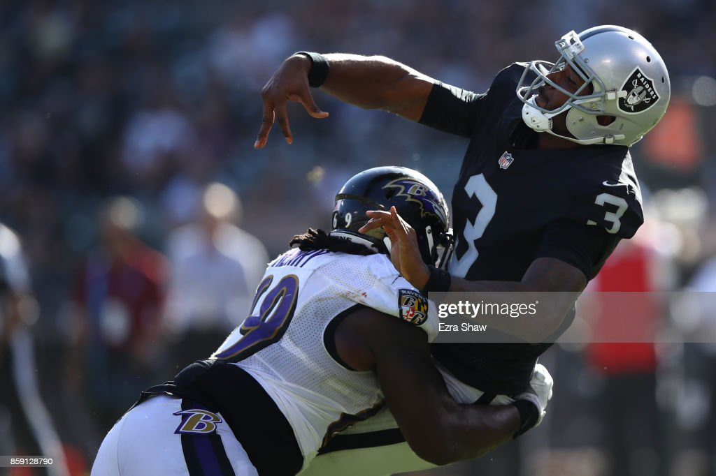 EJ Manuel #3 of the Oakland Raiders is hit by Willie Henry #69 of the Baltimore Ravens during their NFL game at Oakland-Alameda County Coliseum on October 8, 2017 in Oakland, California.