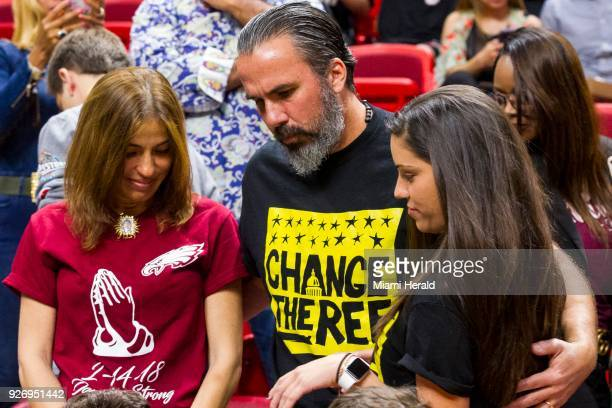Manuel Oliver hugs his daughter Andrea Ghersi as her mom Patricia watches before the Miami Heat faced the Detroit Pistons at the AmericanAirlines...