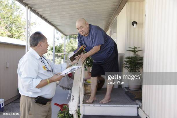 Manuel Palacios of MoveOn visits with Felix Leon while canvassing for Ann Kirkpatrick on November 3 2018 in Tucson Arizona