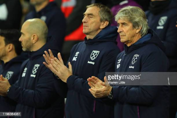 Manuel Pellegrini Manager of West Ham United takes part in a minutes applause in tribute of Martin Peters prior to the Premier League match between...