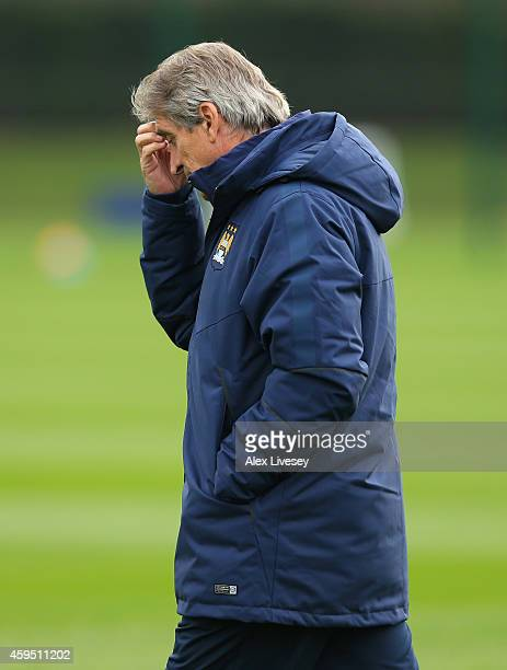 Manuel Pellegrini the manager of Manchester City looks on during a training session at the Manchester City Football Academy on November 24 2014 in...