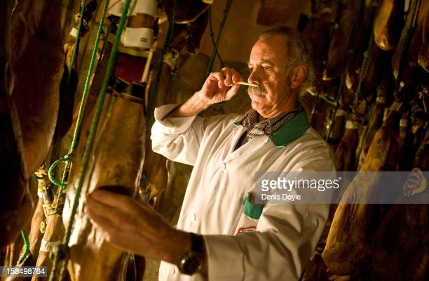 Manuel Revilla checks by smelling a sample of a leg of drycured Jamon Iberico de bellota at his small family jamon business in the town of Guijuelo...