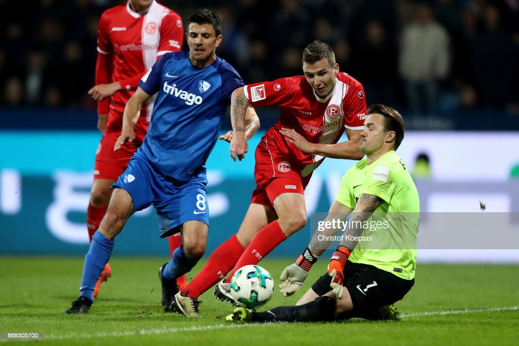 Manuel Riemann of Bochum (R) saves the ball againsat Marcel Sobottka of Duesseldorf (C) during the Second Bundesliga match between VfL Bochum 1848 and Fortuna Duesseldorf at Vonovia Ruhrstadion on October 30, 2017 in Bochum, Germany.