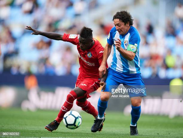 Manuel Rolando Iturra of Malaga CF duels for the ball withgt Amath Ndiaye of Getafe CF during the La Liga match between Malaga CF and Getafe CF at...