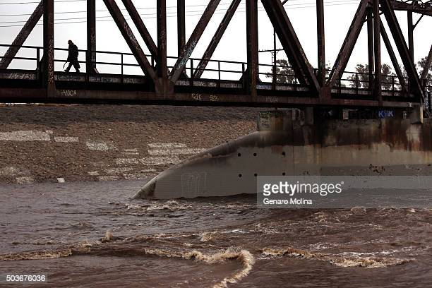 Manuel Sanchez walks along an old Union Pacific Bridge as the Los Angeles river churns in South Gate on January 6 2016