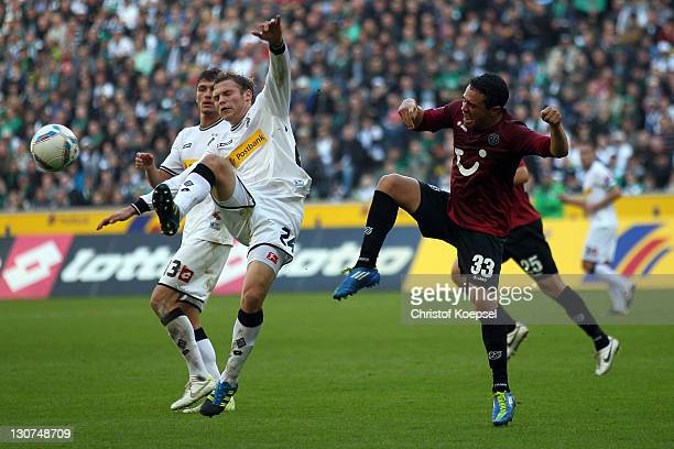 Manuel Schmiedebach of Hannover challenges Tony Jantschke of Moenchengladbach during the Bundesliga match between Borussia Moenchengladbach and...