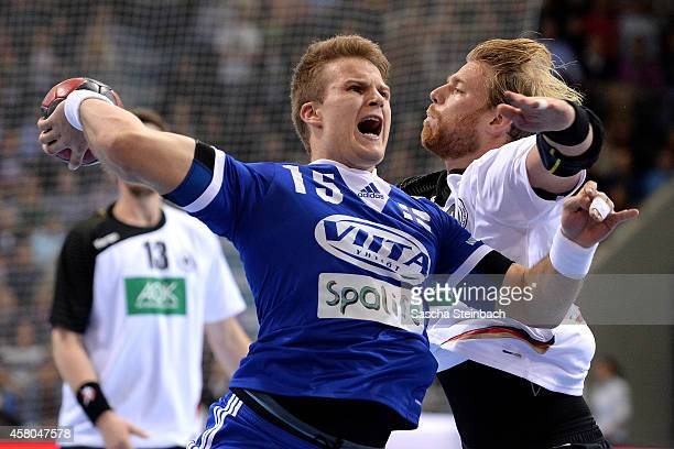 Manuel Spaeth of Germany is challenged by Richard Sundberg of Finland during the 2016 European Men's Handball Championship qualifier match between...